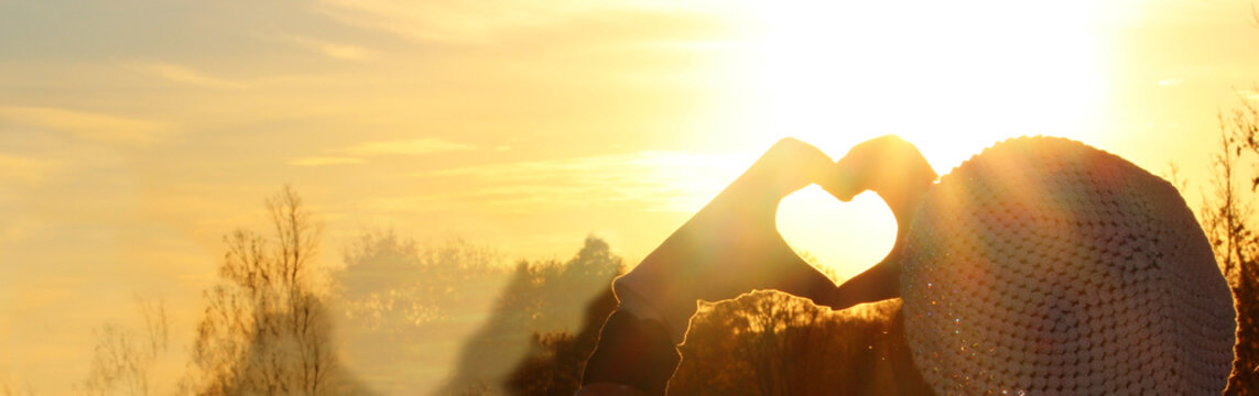 Heart Symbol.  Woman hands in gloves heart symbol shaped, on a beautiful sunset light background.