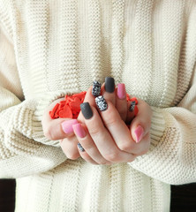 A handful of small hearts in the girl`s hands. The girl is wearing a knitted sweater