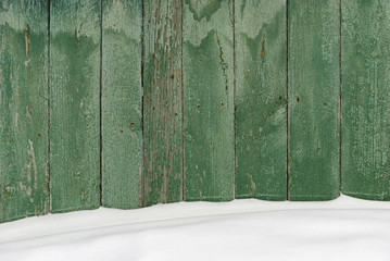 Wooden fence covered with snow.