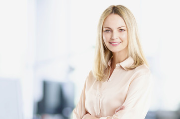 Professional female in office. Shot of a middle aged pretty businesswoman standing in her office while looking at camera and smiling.