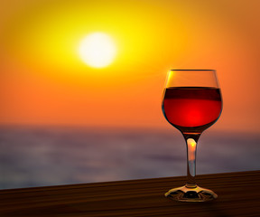 Red wine glass at the summer sunset romantic background.