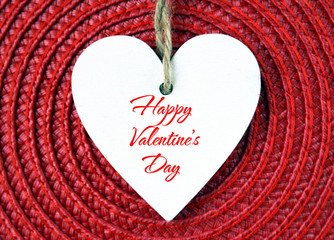 Happy Valentines Day background.Decorative white wooden heart on red straw napkin.Selective focus.Saint Valentine's Day or Love concept.