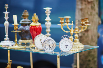Old alarm clocks and candle holders on flea market in Paris