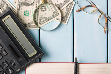 Business concept. Magnifying glass with glasses, dollar bills, notebook, fountain pen and calculator on blue wooden background