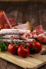 Food tray with delicious salami, pieces of sliced ham, sausage,