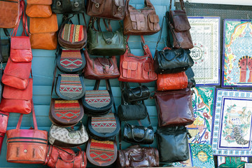 colored leather and textile bag on the wall of store