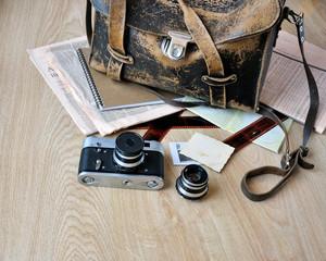 Old camera, film, lens and vintage satchel on wooden background.