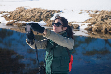 brunette woman with green, red and brown clothes with camera, as photographer taking selfie photo picture, in winter snow Gredos mountain, Avila, Spain, Europe