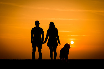 Silhouette lovers couple with dog on sunset dusk sky background. black shadow of people, hug and kiss, family: passion in love concept: decoration,design,valentines, family