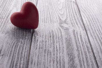 Red Heart on the white painted wooden background.