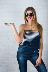 Beautiful female model in jeans. Open hand with pointing
