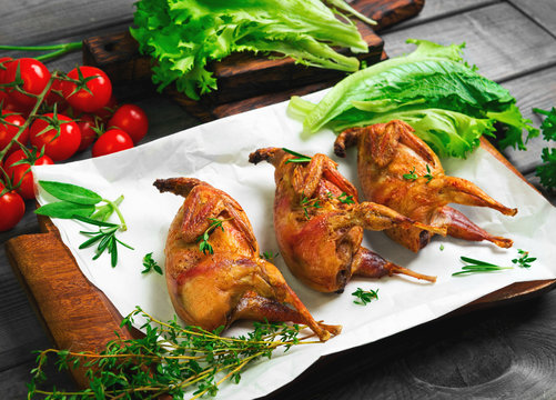 Roasted quail on a wooden tray