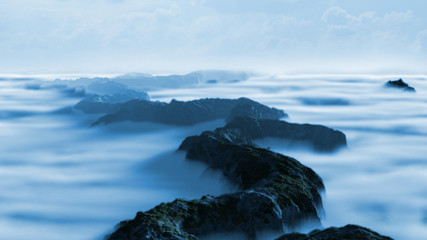 bluish serene mountain landscape with low crawling clouds