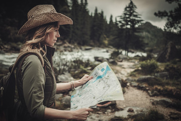 Woman hiker, searching right direction on map near wild mountain river.