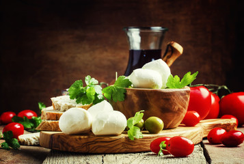 Mozzarella cheese, bread, olives and tomatoes, snack plate. Vint