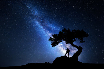 Milky Way. Night sky with stars, old tree and silhouette of a standing alone man with backpack on the mountain. Blue milky way and traveler. Travel background. Silhouette of a man under the tree