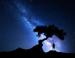 Milky Way. Night sky with stars, old tree and silhouette of a standing alone man on the mountain. Blue milky way with light and man. Travel background. Silhouette of a man under the tree. Universe