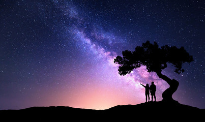 Milky Way with people under the tree on the hill. Landscape with night starry sky and silhouette of standing happy man and woman who pointing finger in starry sky. Milky way with travelers. Universe