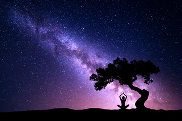 Milky Way with tree and silhouette of a sitting woman practicing yoga. Beautiful landscape with meditating girl under the tree against starry sky with purple milky way. Galaxy. Beautiful universe