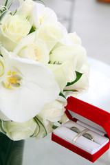 wedding rings in red box and bride's bouquet