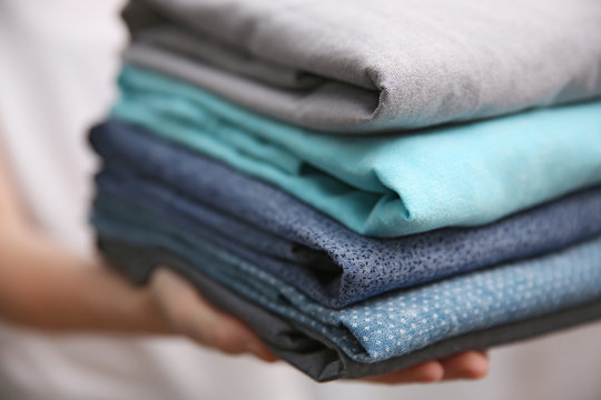 Woman holding folded clothes in hands, closeup