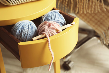 Knitting yarn and hook in yellow table drawer, closeup