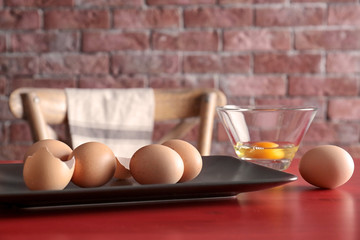 Raw eggs on plate on wooden table