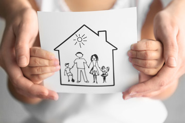 Child and adult person holding drawing of house with family, closeup. Adoption concept