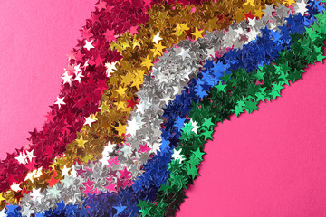 Bright confetti in shape of stars on pink background, close up