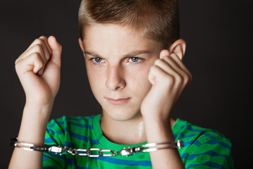 Boy chained in handcuffs