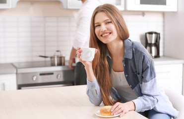 Beautiful young woman drinking coffee in kitchen at home
