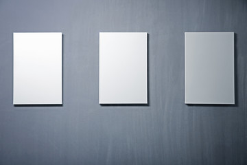 Empty white canvases on gray wall background