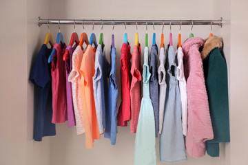 Colourful clothes on hangers in wardrobe
