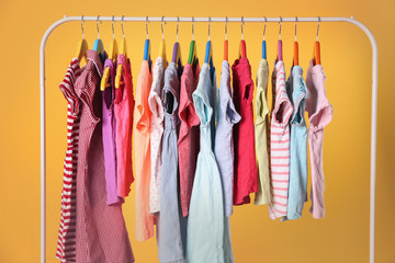 Hangers with colourful clothes on yellow background