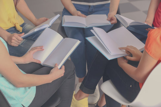 Group of people reading books indoors, closeup