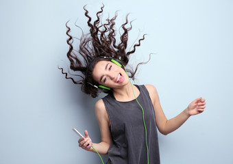 Beautiful young woman in headphones listening to music and singing on light background