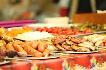 Tray with different kinds of sausages on counter