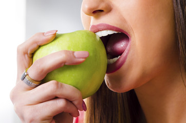 Closeup, young woman with perfect teeth biting green apple