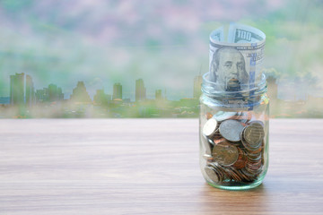 Dollar coin and banknote cash saving in glass jar, with city building background, finance saving concept
