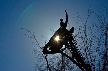Silhouette of giraffe sculpture with sun glaring through eye