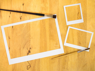 White paper frame on wood background with paintbrush.