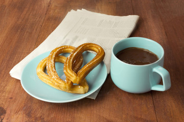 Spanish churros, chocolate, blurred newspaper, and copyspace