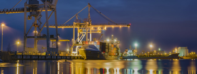 unloading cargo ship with containers in sea port at night - fototapety na wymiar