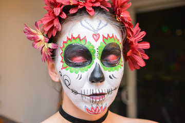 Young girl face painting for halloween mexican style. Mexican death