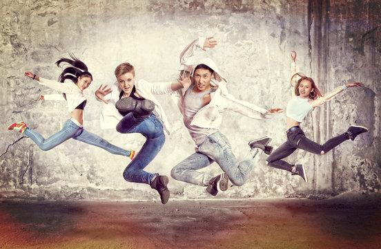 Modern dancing group practice dancing in front wall
