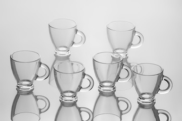 Set of six empty cups of tea with handle isolated on white blurred background