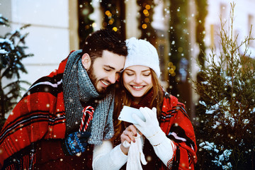 Outdoor. Young beautiful happy smiling couple using smart phone. Models looking at screen, bundled up in tartan blanket, wearing stylish clothes. Winter holidays, Christmas, New Year concept. Waist up