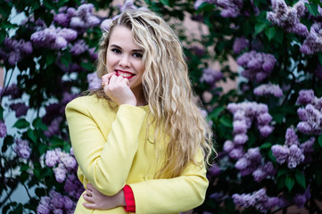 Blonde girl in a yellow coat stands against the backdrop of blooming lilacs in spring