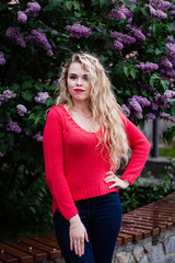 Blonde girl in a yred sweater stands against the backdrop of blooming lilacs in spring