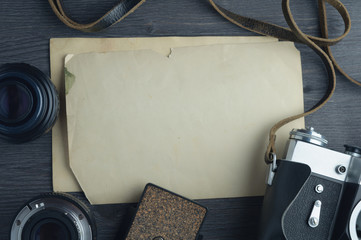 Old camera and lenses on dark wooden background